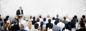 Public speaker or business presenters showing confidence in front of a large group.